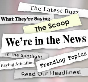 We're in the News words on newspaper headlines with other phrases like Paying attention, the latest buzz, scoop, trending topics, in the spotlight and more