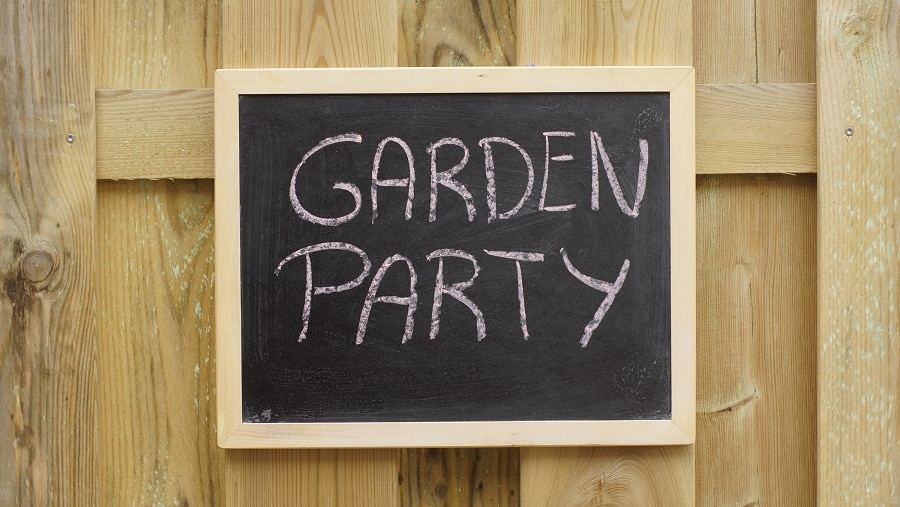Garden party written on a chalkboard hanging at a  wooden wall