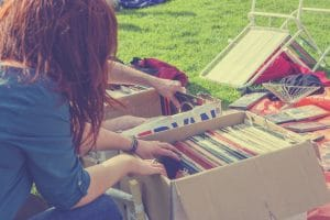 Young hipster girl browsing through second hand records in boxes on a free market in the Netherlands