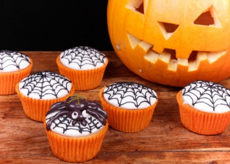 Halloween themed cupcakes with a black spider web iced over white icing, held in orange cupcake cases.