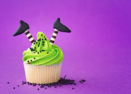 Green iced cupcake with witches legs and feet sticking out