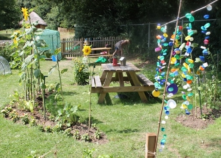 Midfield Primary School garden's picnic table surrounded by sunflowers and brightly coloured suncatchers