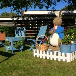 Large knitted Peter Rabbit eating basket of produce next to plant pots