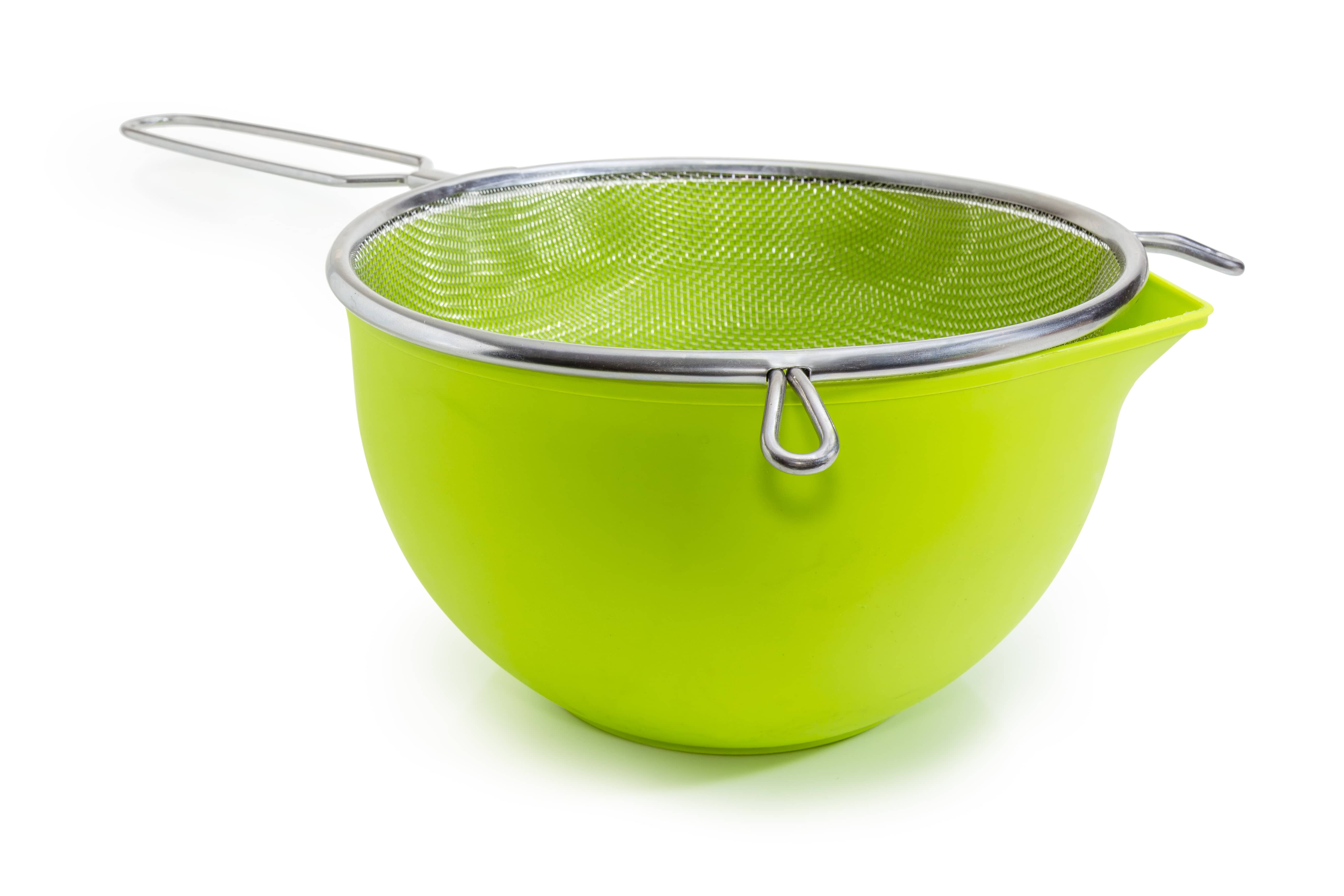 Green bowl and round stainless steel sieve with wire mesh at selective focus on a white background