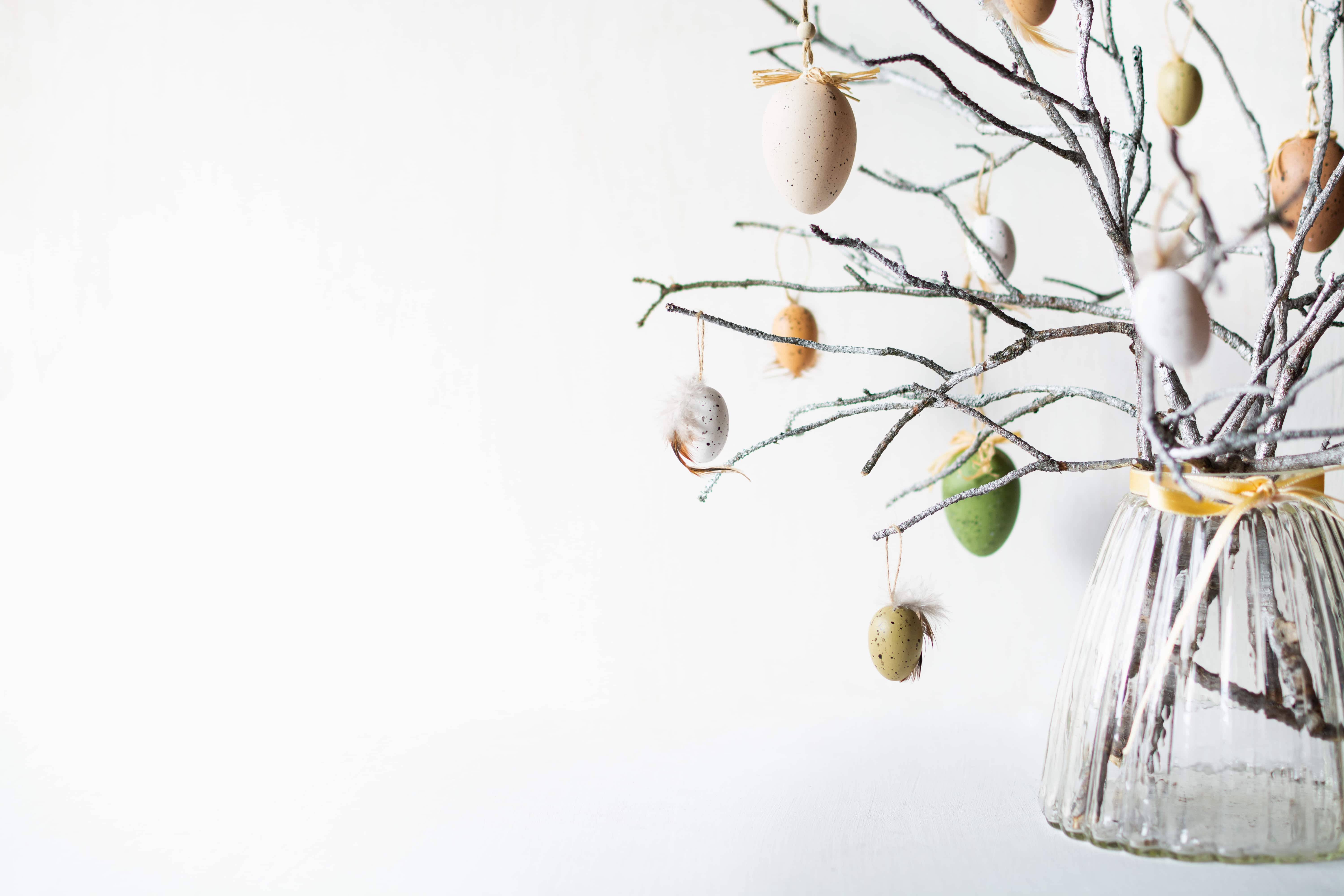 Still life with tree branches decorated with Easter eggs and feathers in a glass vase