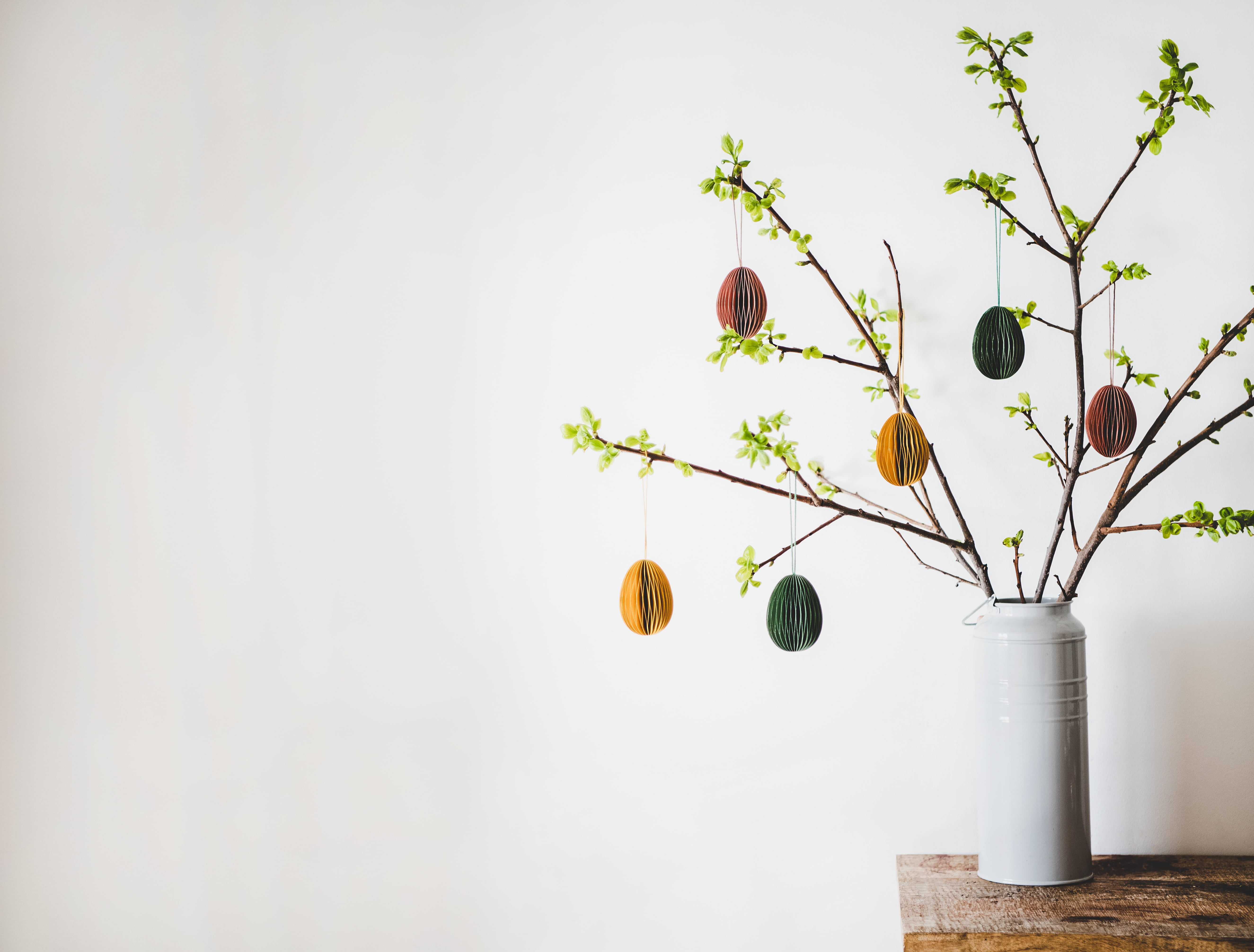 Easter holiday home decoration. Tree branches in vase with fresh spring leaves decorated with festive colorful Easter eggs, white wall background, copy space. Easter holiday preparation, greeting card