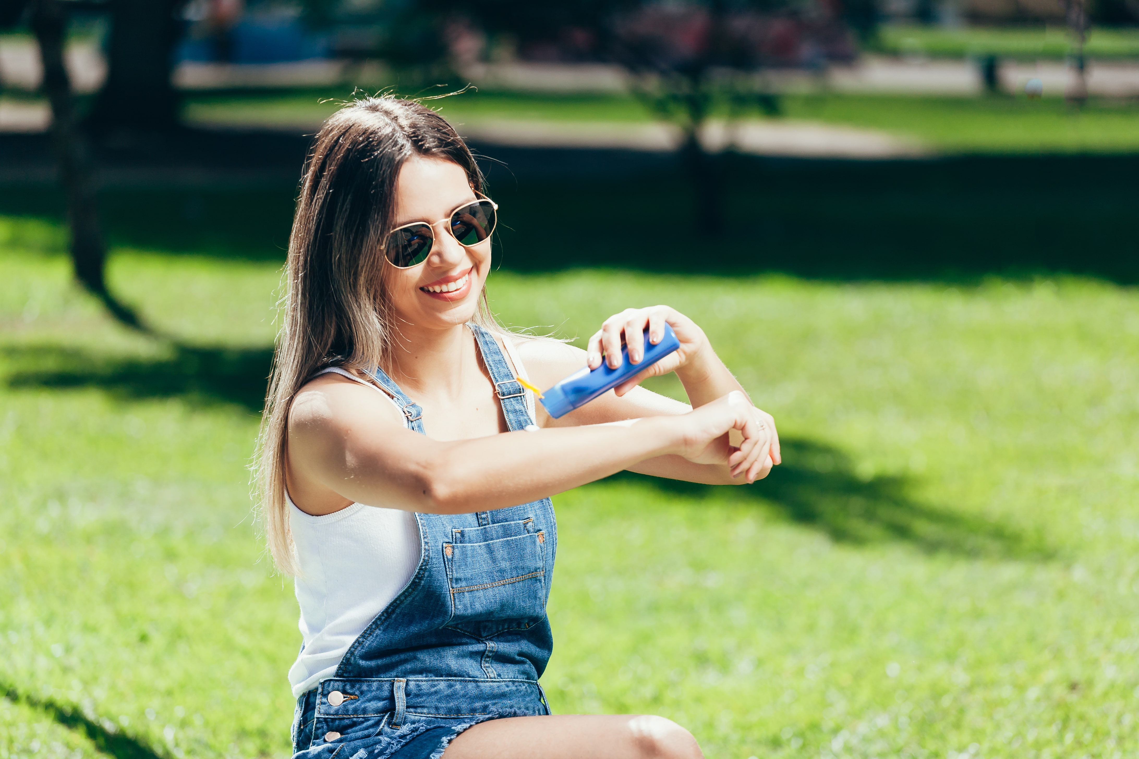 Young woman with sunscreen and sunglasses outside on a beautiful summer day