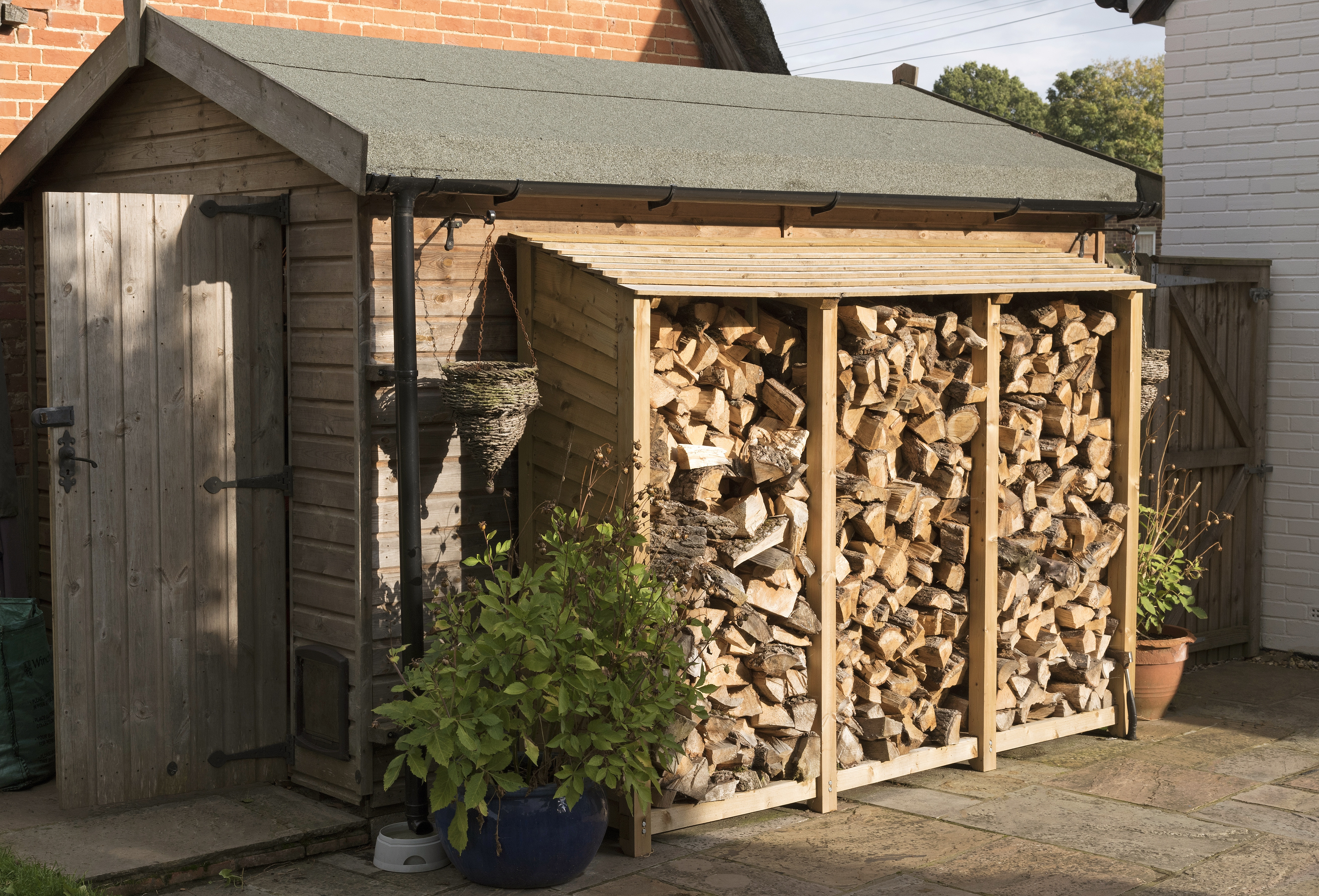 Log store standing against a garden shed