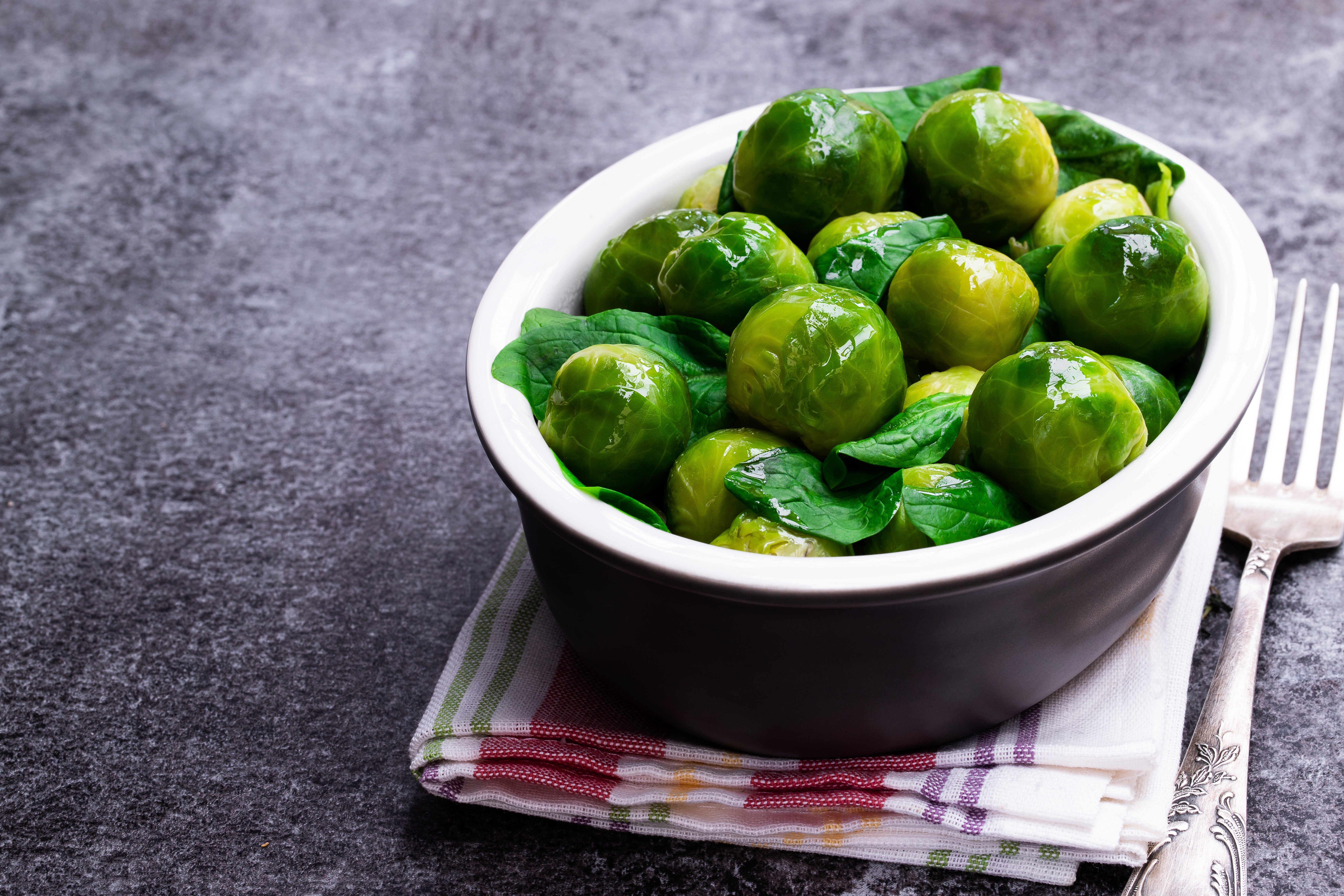 Cooked  brussels sprouts with spinach on gray table