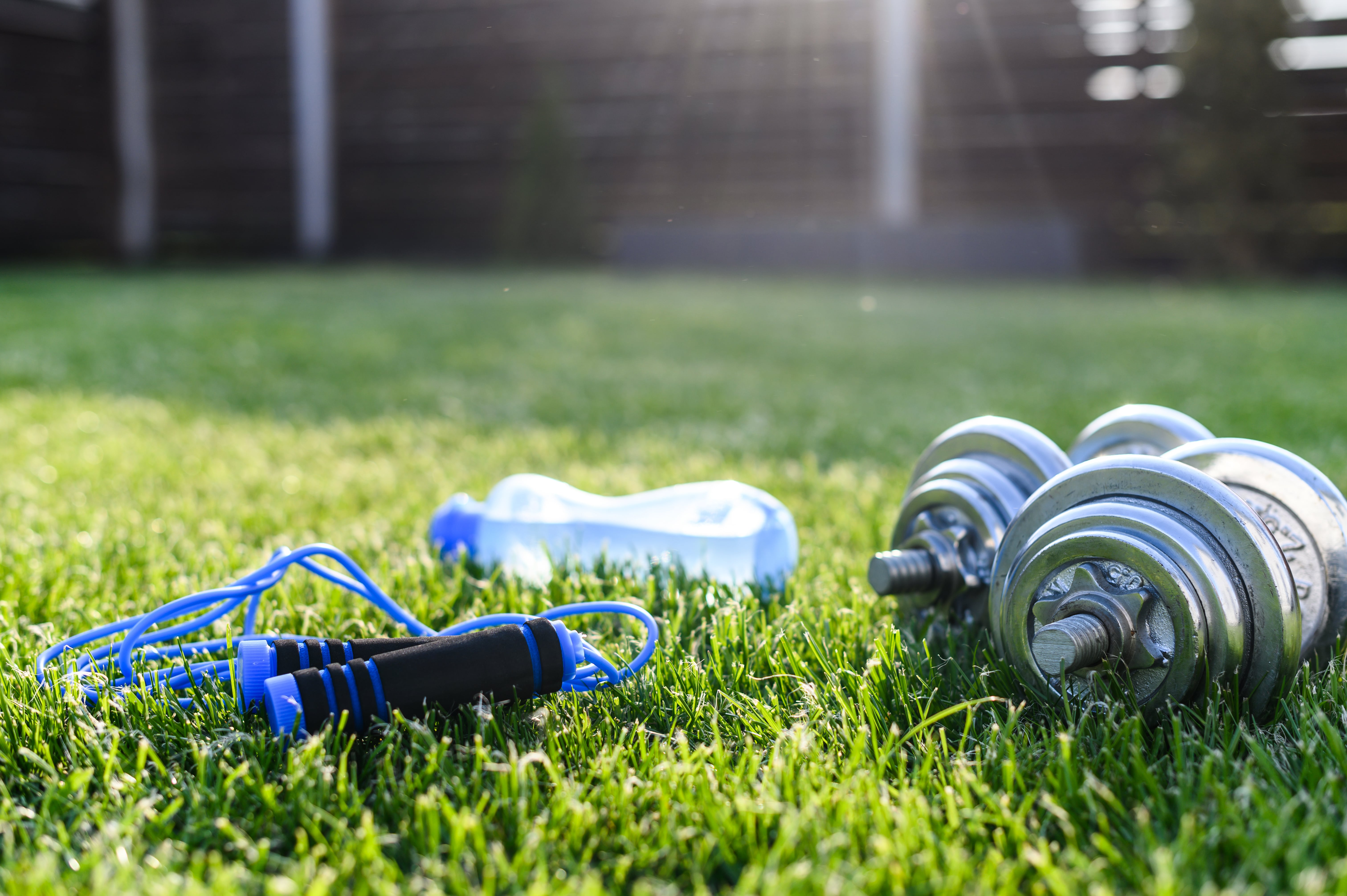 Workout in the backyard. Iron dumbbells, sports bottle of water and jump rope on the greenlawn