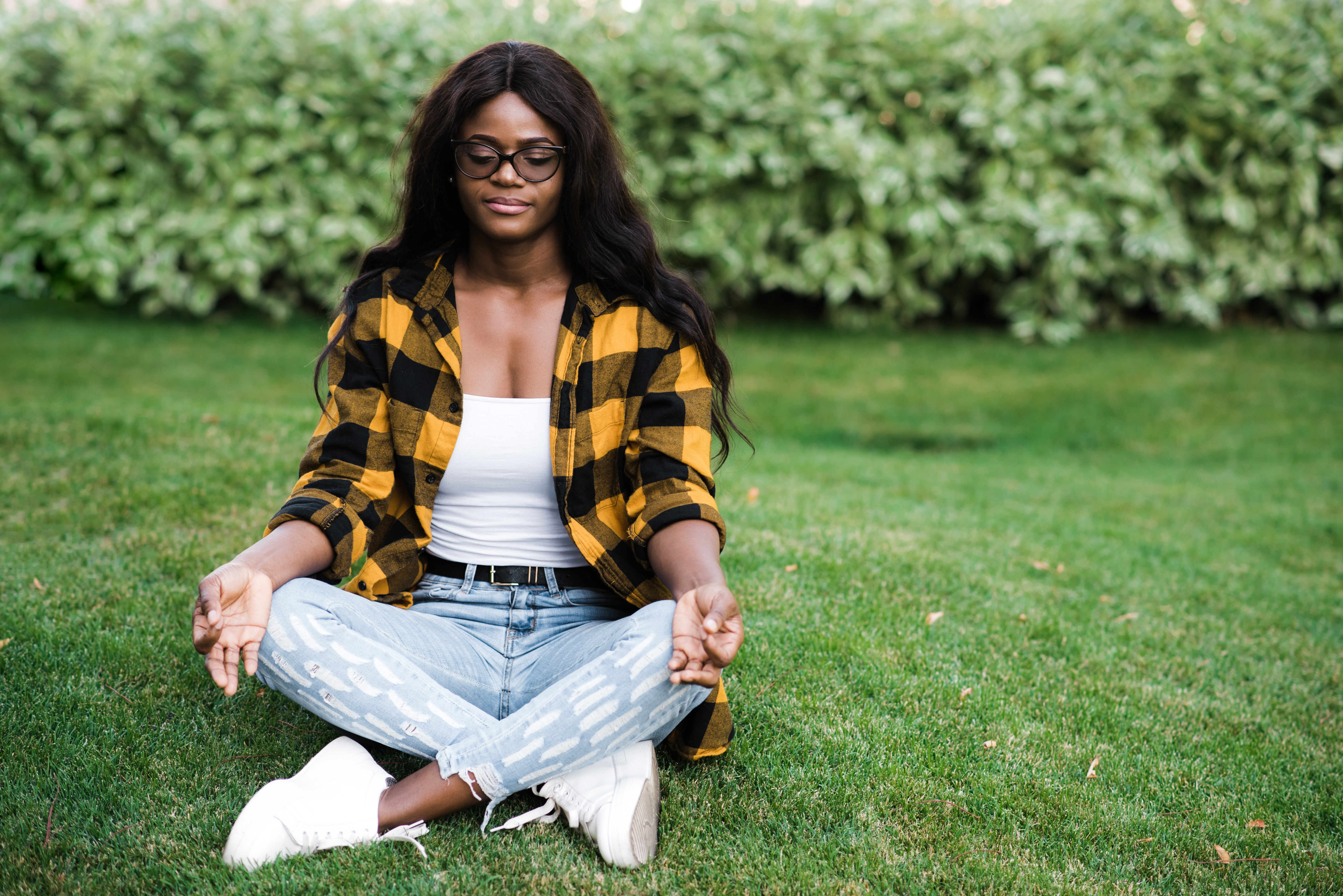 Young African American woman dressed in stylish casual clothes meditates in the park while sitting on the grass in lotus position with closed eyes