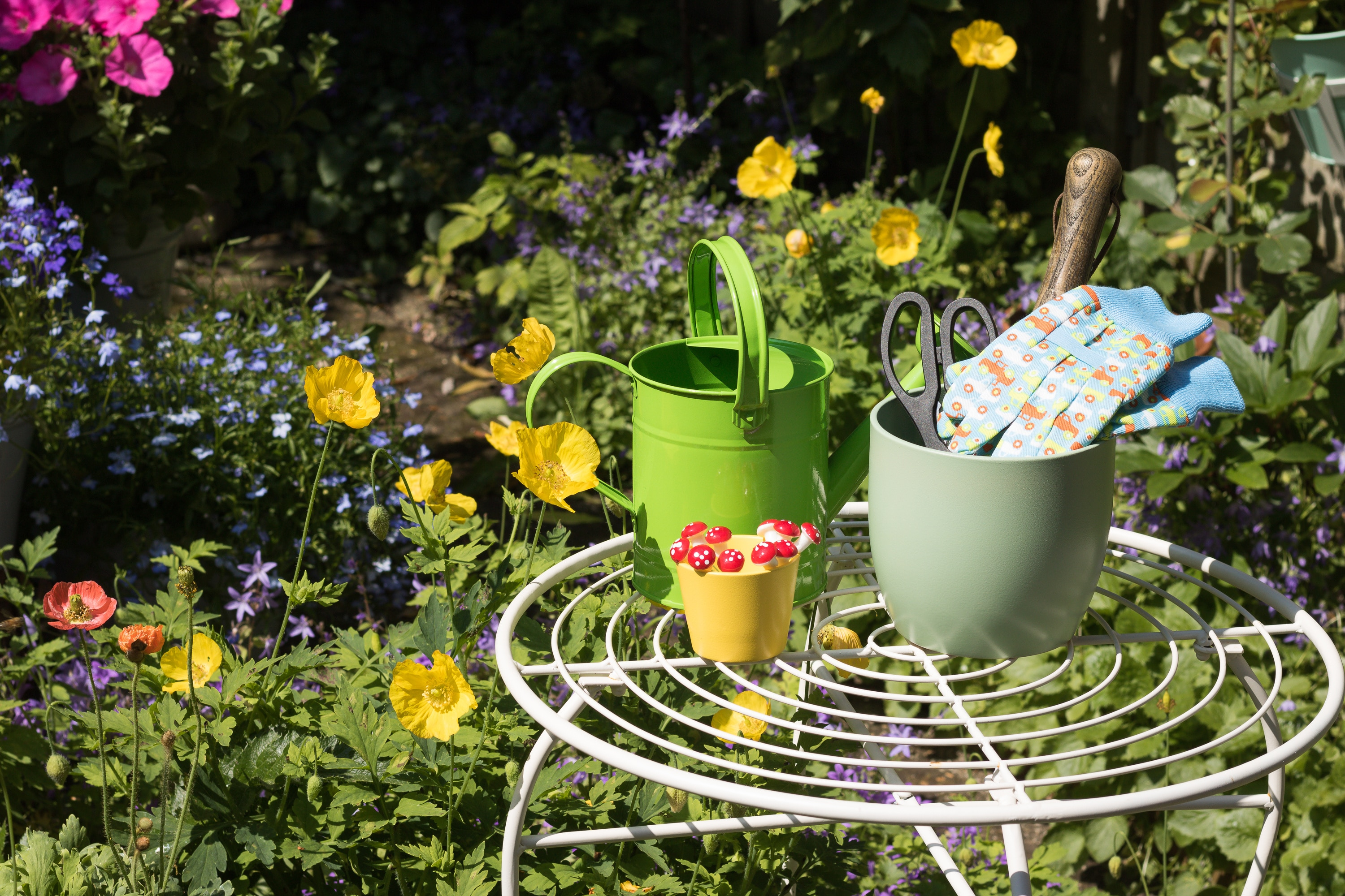 View of colorful flowering summer garden. Garden tools, gloves, flower pots, watering can is on a garden table among growing flowers on a sunny day. Concept: gardening.