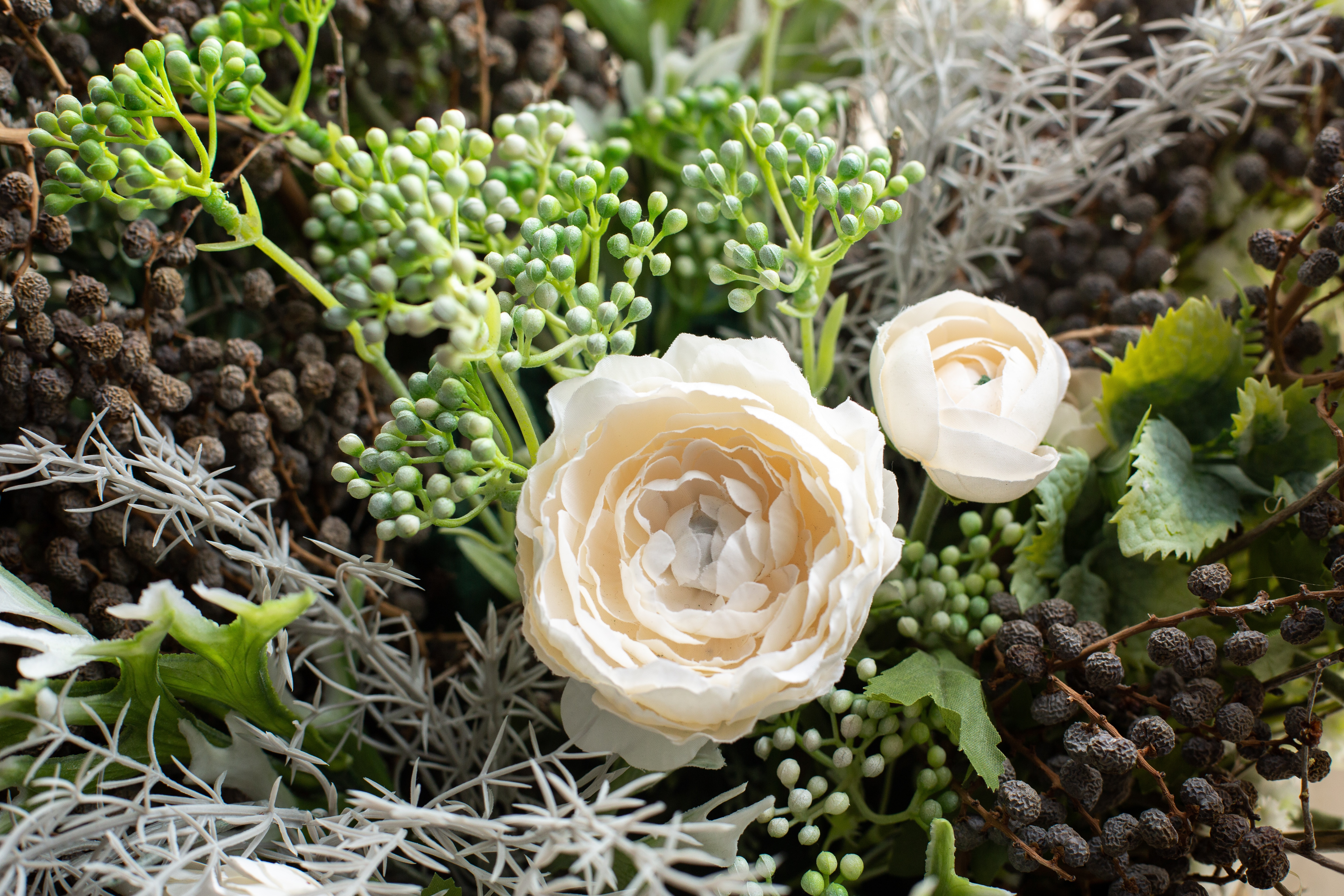 Arrangement of white flowers and dried flowers in a wicker basket side view