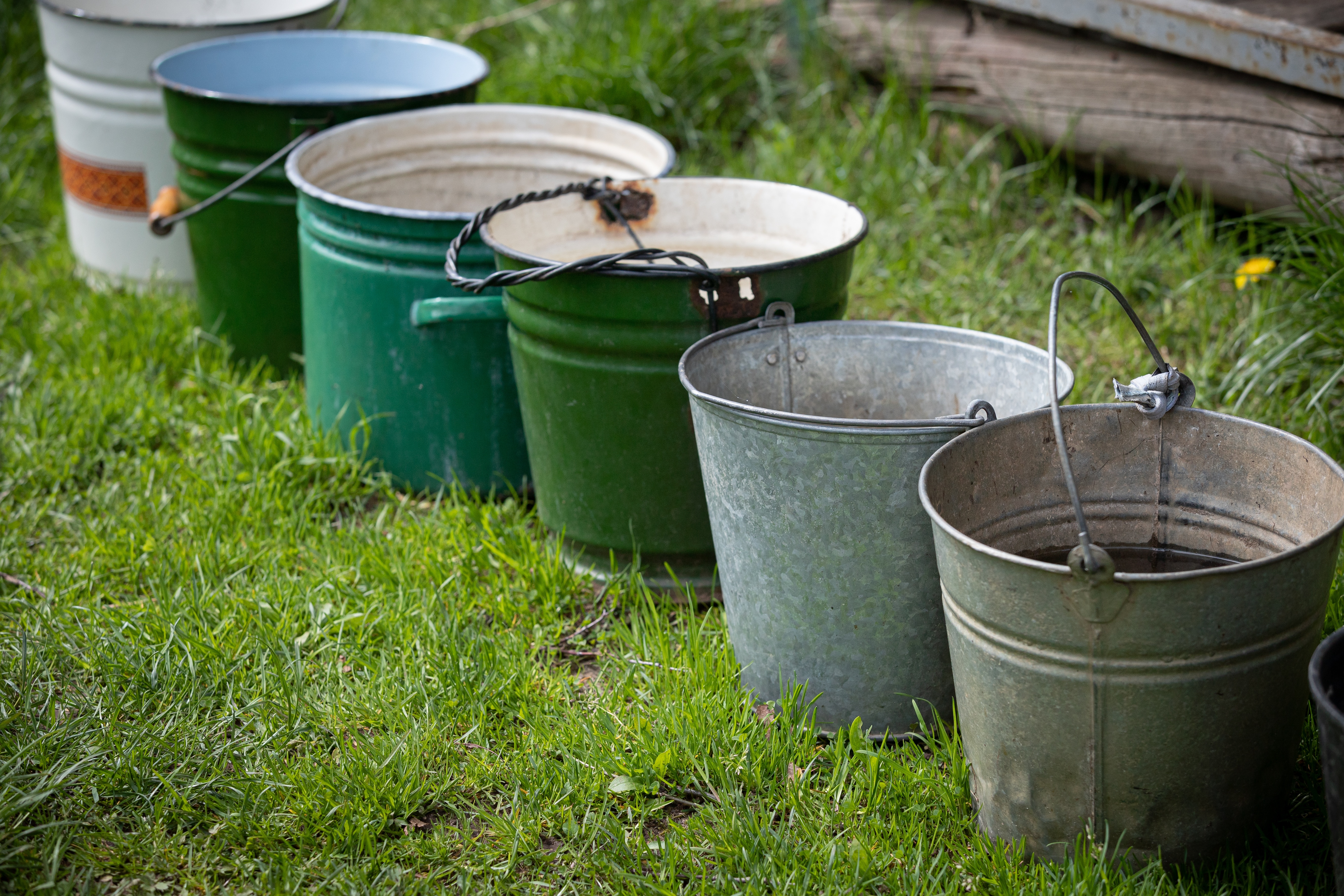 Many different buckets stand in a row to collect rainwater. Buckets of water stand on the grass in the garden next to the house. Village concept