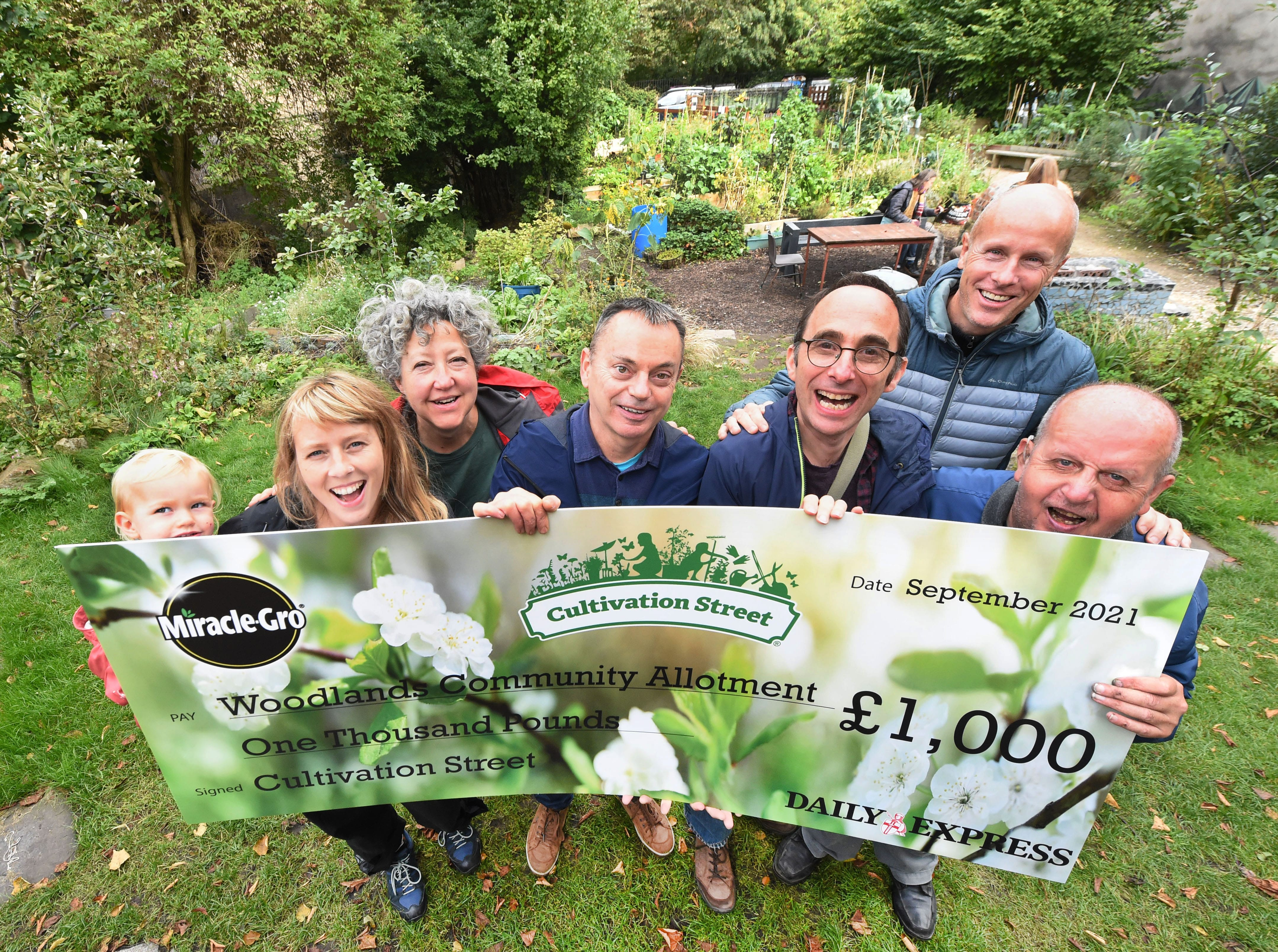 D.EXPRESS: Tim Cowen and locals at the Woodlands Community Garden, Ashley Street, Glasgow, who have won the £1,000 Community Garden category in the Cultivation Street gardening competition with David Domoney and Miracle-Grow.