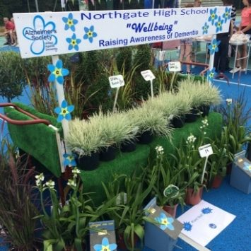 "Northgate High School well being plant stall, sign reading ""Raising Awareness of Dementia"""